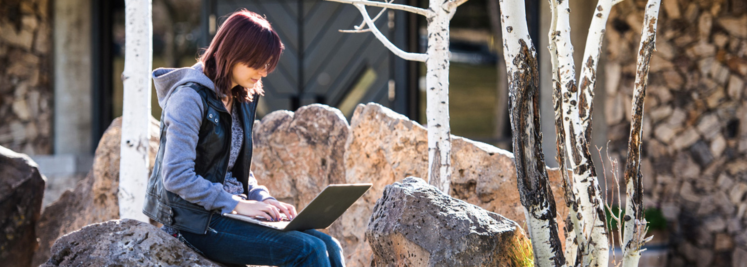 Student sitting with laptop computer outdoors on campus